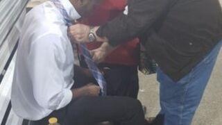 Para staruszków uczy młodego mężczyznę, jak wiązać krawat.