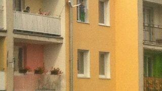 Pięciolatek stoi na parapecie okna, a mamuśka baluje na balkonie