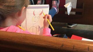Znudzona dziewczynka rysuje sobie w kościele