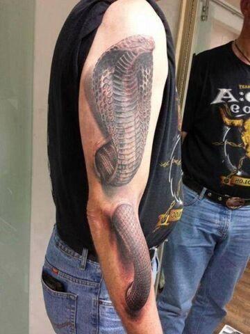 Kobra królewska na ręce. Tatuaż 3d