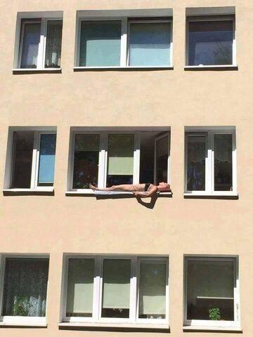 Dziewczyna opala się na parapecie za oknem