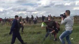 Kamerzystka podstawia nogę biegnącemu imigrantowi z dzieckiem