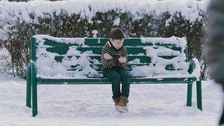 Chłodna reakcja na Chłopiec bez kurtki na ławce