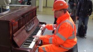 Budowlaniec gra na pianinie na jednej z londyńskich stacji kolejowych