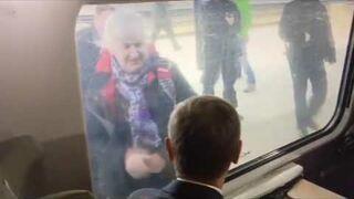 Starsza kobieta pozdrawia Donalda Tuska. Przez na migi przez szybę pociągu