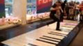 Dwie dziewczyny grają na gigantycznym pianinie nogami