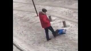 Ojciec kopie dziecko które nie chce wstać ze śniegu