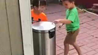 Dzieci bawią się klapą od kasza na śmieci