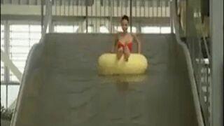 Zabawa biuściastej pani na basenowej zjeżdżalni