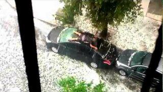 Gość osłania swoje auto przed gradem