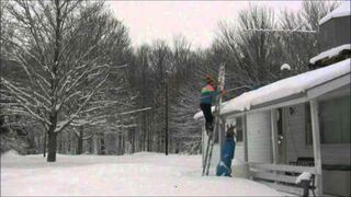 Facet stara się usunąć śnieg z dachu