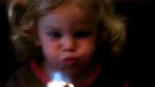 Dziewczynka usiłuje zgasić świeczkę