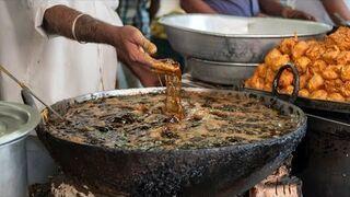 Hinduski szef kuchni wyciąga potrawy z wrzącego oleju gołą ręką