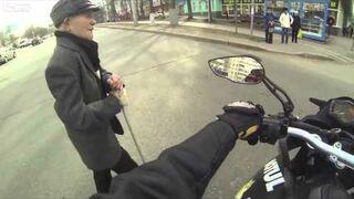 Motocyklista pomaga przejść dziadkowi przez drogę