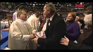 Tadeusz Rydzyk (szybkie ręce) przyjmuje datki od swoich wiernych